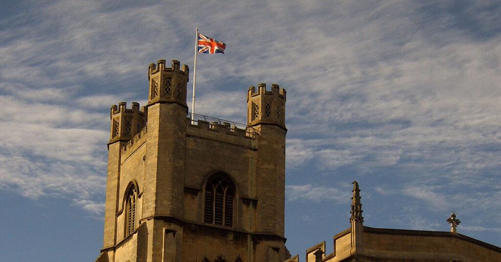 Der Union Jack flattert vor bewölktem Himmel auf dem Kirchturm von Great St. Mary's in Cambridge