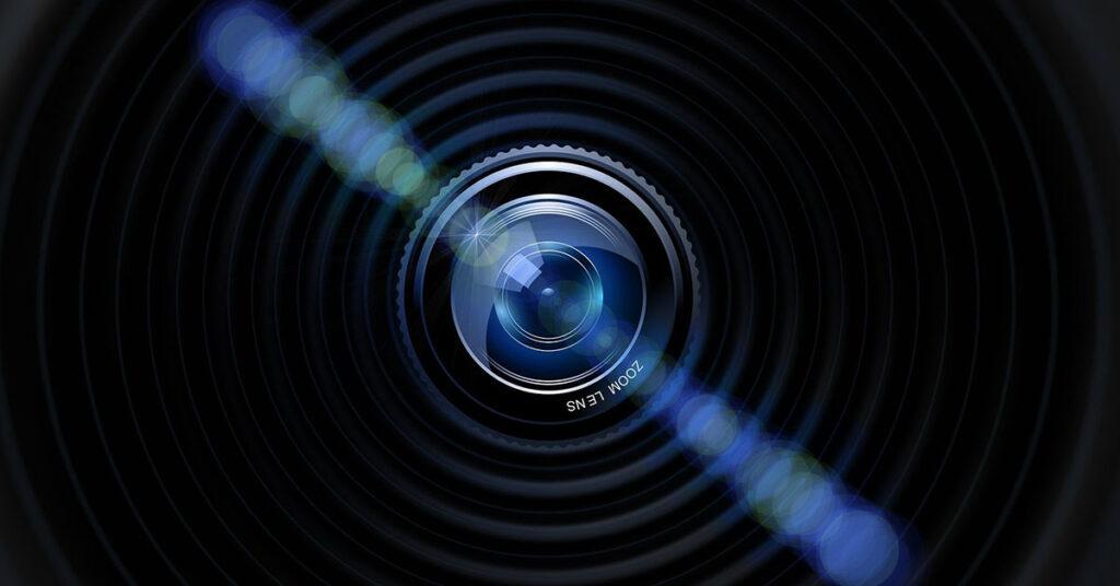Eine Kameralinse im Dunkeln mit blauem Lensflare.