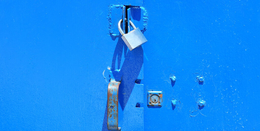 Ein silbernes Schloss an einem blauen Stahlkasten