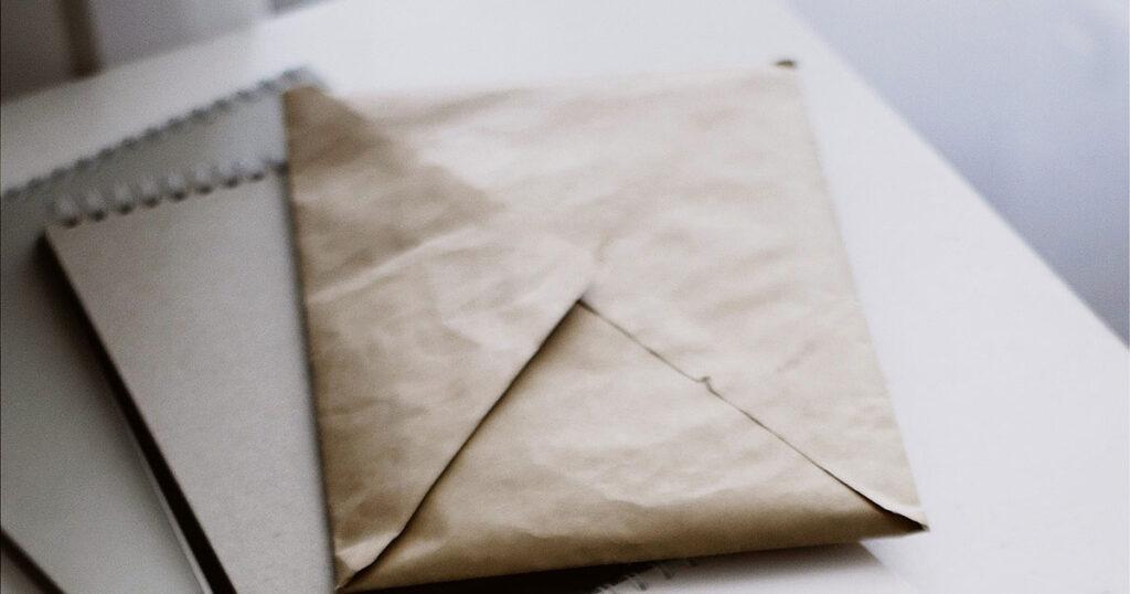 Ein Umschlag liegt auf einem Stapel Notizblöcke.