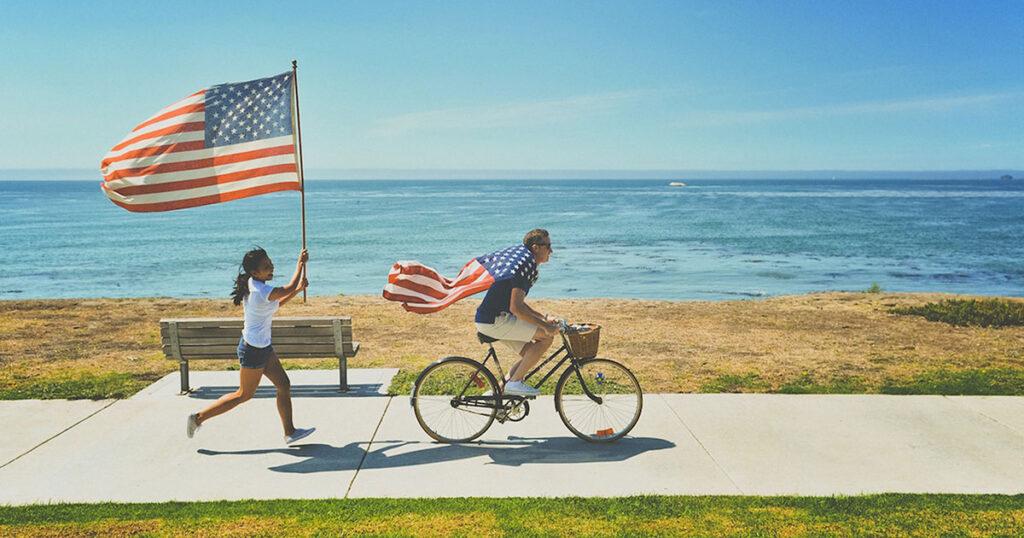 Ein Mann mit einer US-Flagge als Umhang wird von einer laufenden Frau mit US-Flagge verfolgt. Am Horizont erkennt man keinen Nachfolger für Privacy Shield.