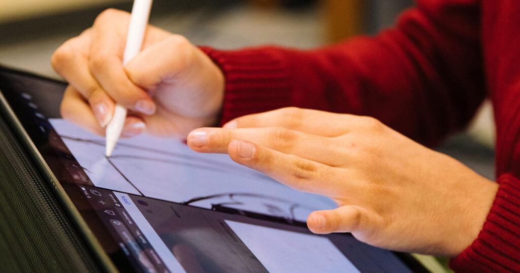 Ein Kind zeichnet etwas auf einem Tablet, nur die Hände, der Stylus und das Tablet sind zu sehen.
