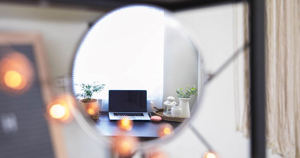 Ein Laptop spiegelt sich in einem runden Spiegel.