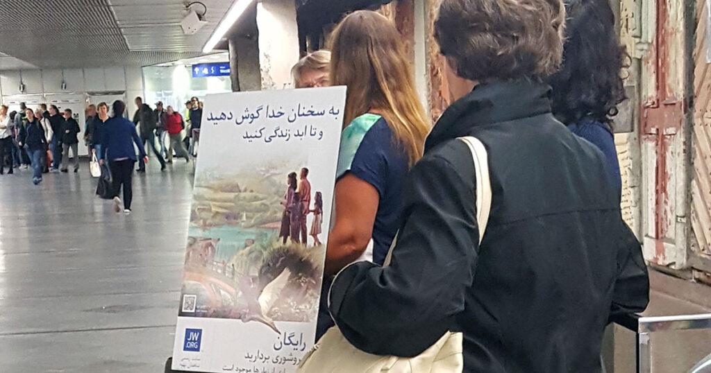 Drei weibliche Mitglieder der Zeugen Jehovas in einer Bahnhofsunterführung mit Informationsmaterial auf Arabisch.