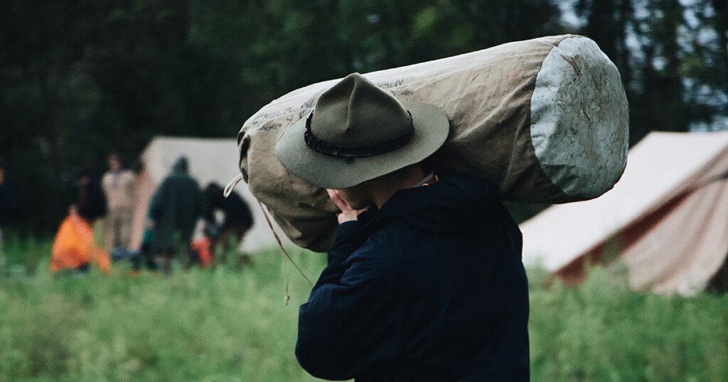 Ein Pfadfinder trägt einen Seesack in Richtung einer Gruppe von Menschen vor einem Zelt. Er ist von hinten zu sehen, die Gruppe dank fehlender Tiefenschärfe nicht identifizierbar.