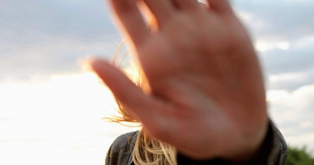 Eine Hand vor einem Gesicht