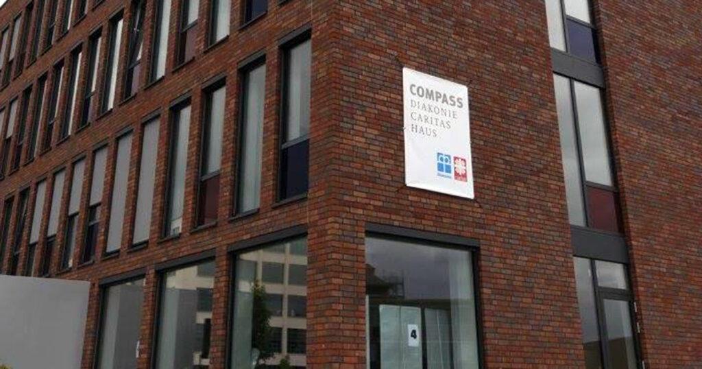 Schild mit der Aufschrift »COMPASS Diakonie Caritas Haus«