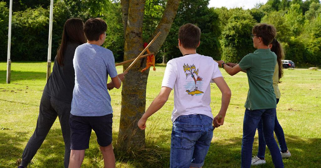 Vier Kinder spielen mit Stöcken und einem Gummihuhn