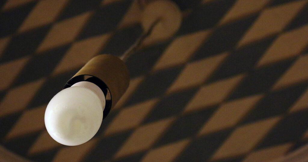 Eine Glühbirne ohne Lampenschirm hängt an einem Kabel von einer Decke mit weiß-blauen Rauten herab.