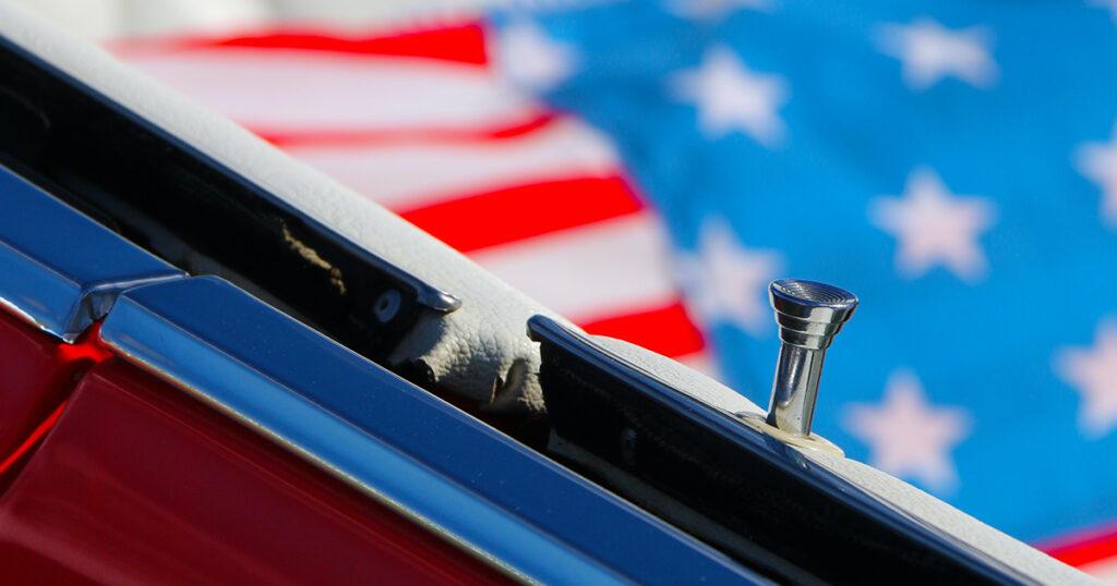 Ein Verriegelungsknopf an einem Oldtimer, im Hintergrund eine US-Flagge.